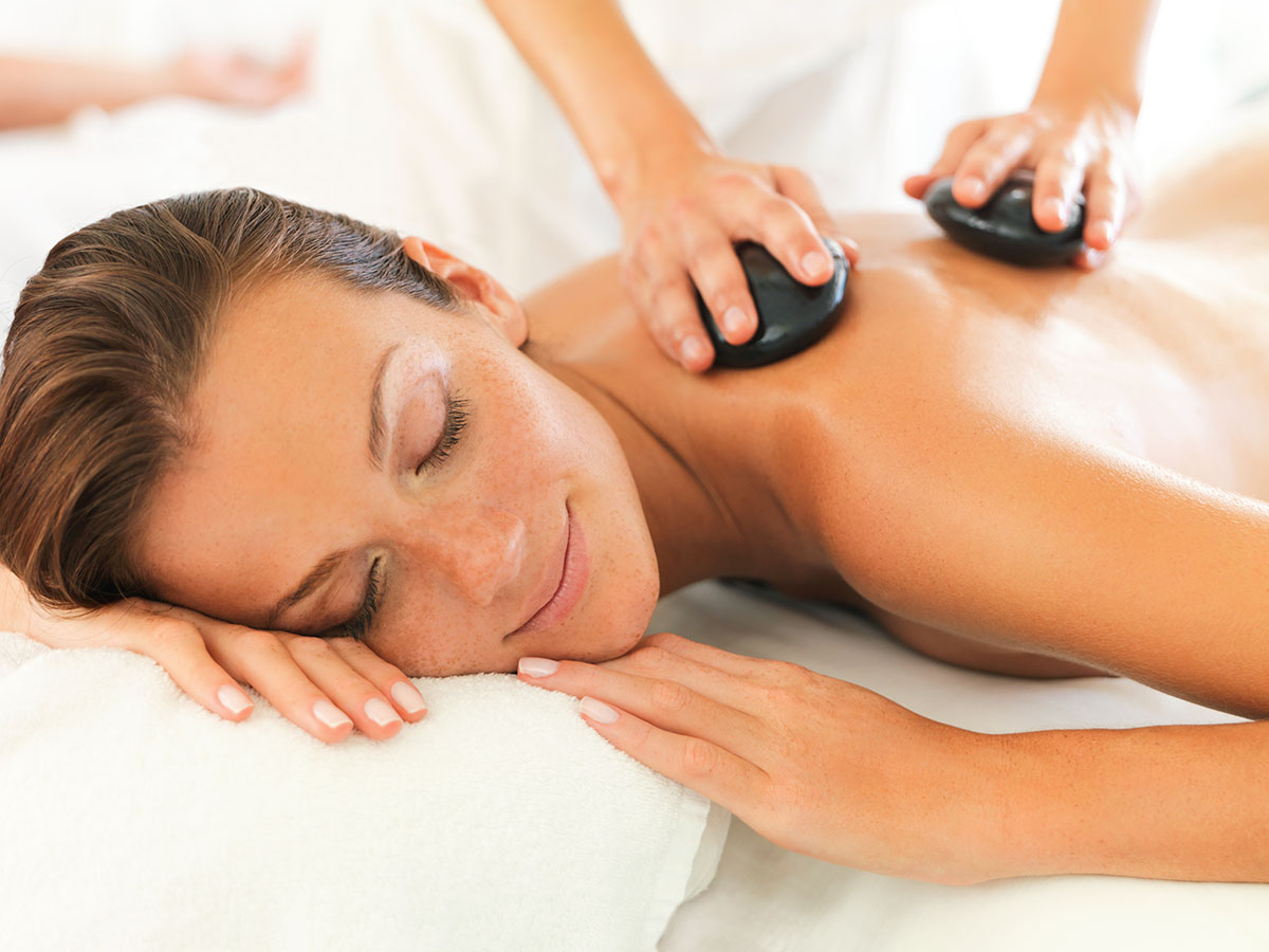 Attractive young woman smiling while having a hotstone massage